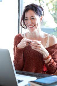 Femme se préparant à effectuer sa séance de sophrologie en ligne via son ordinateur
